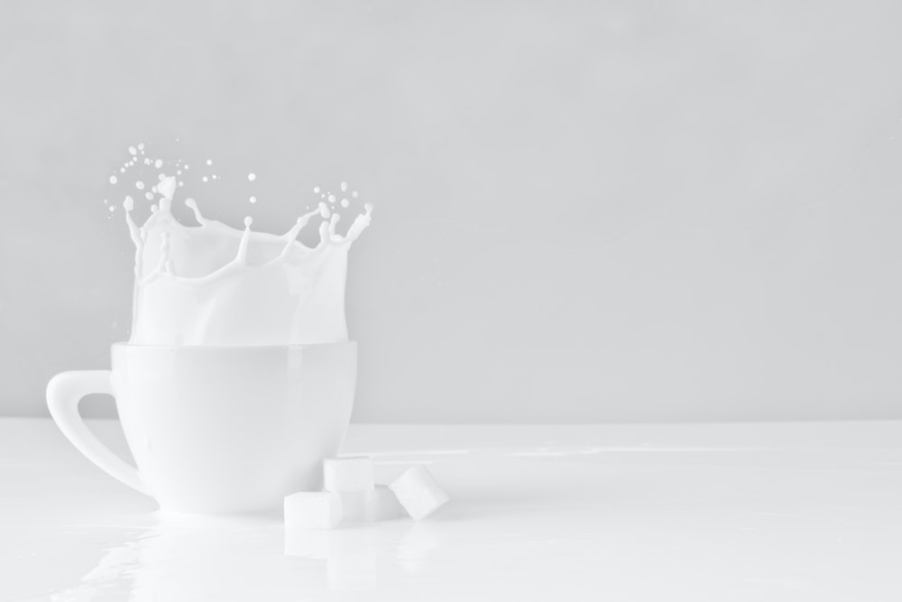 sugar block dropped on white cup with milk