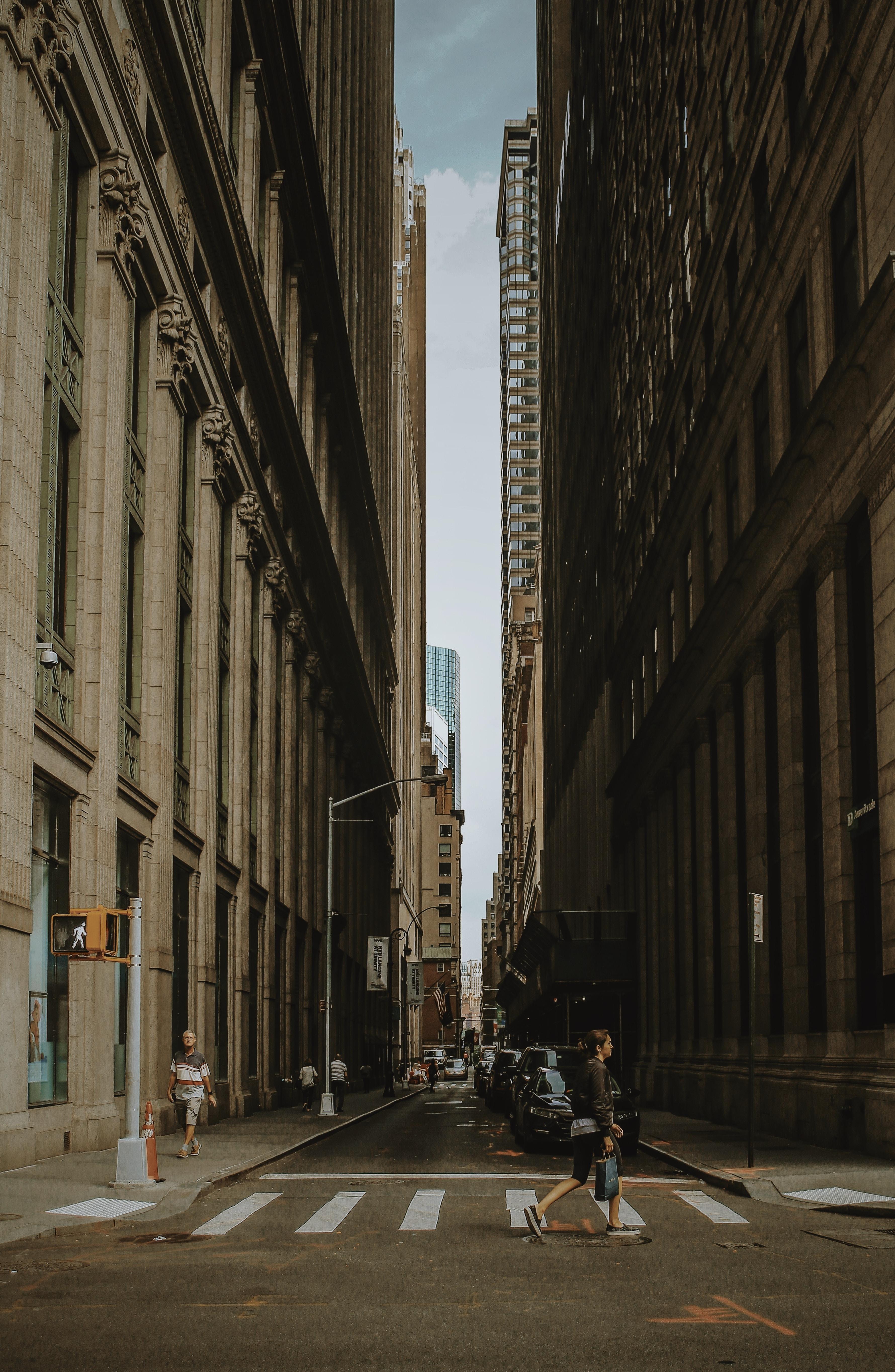 woman walking on street between building during daytime