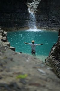 man standing beside body of water