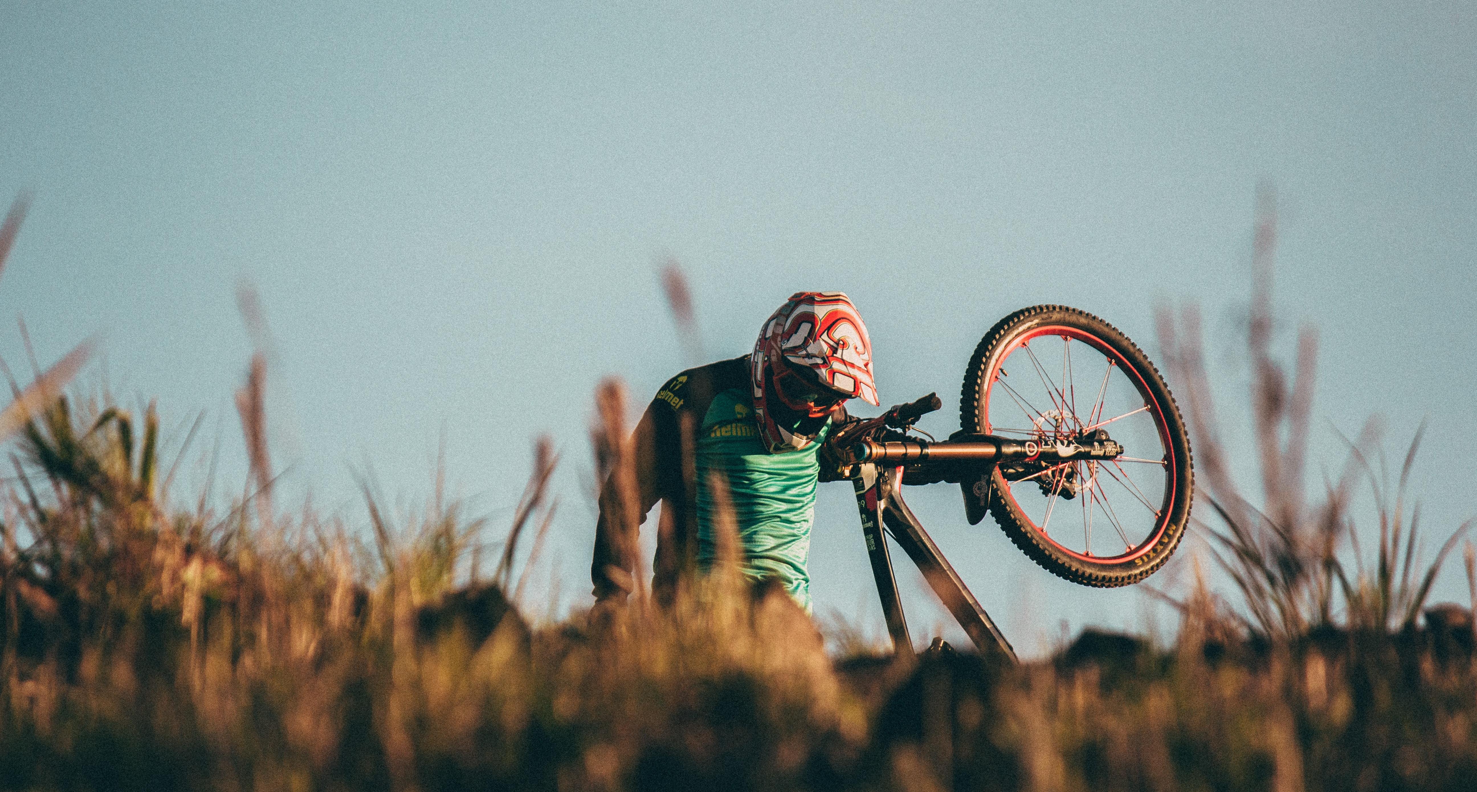 man carrying black mountain bike uphill