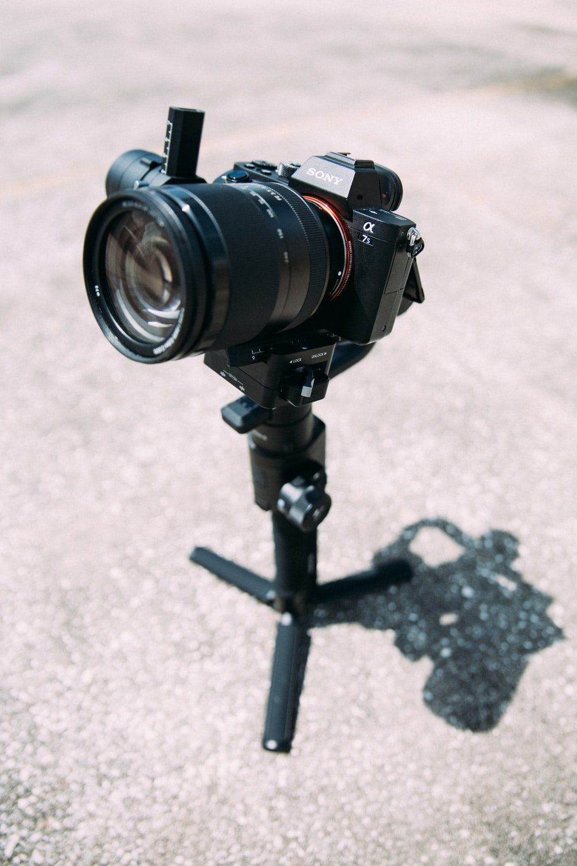 black DSLR camera on tripod stand