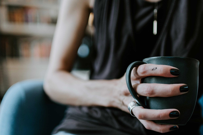 person holding green ceramic mug