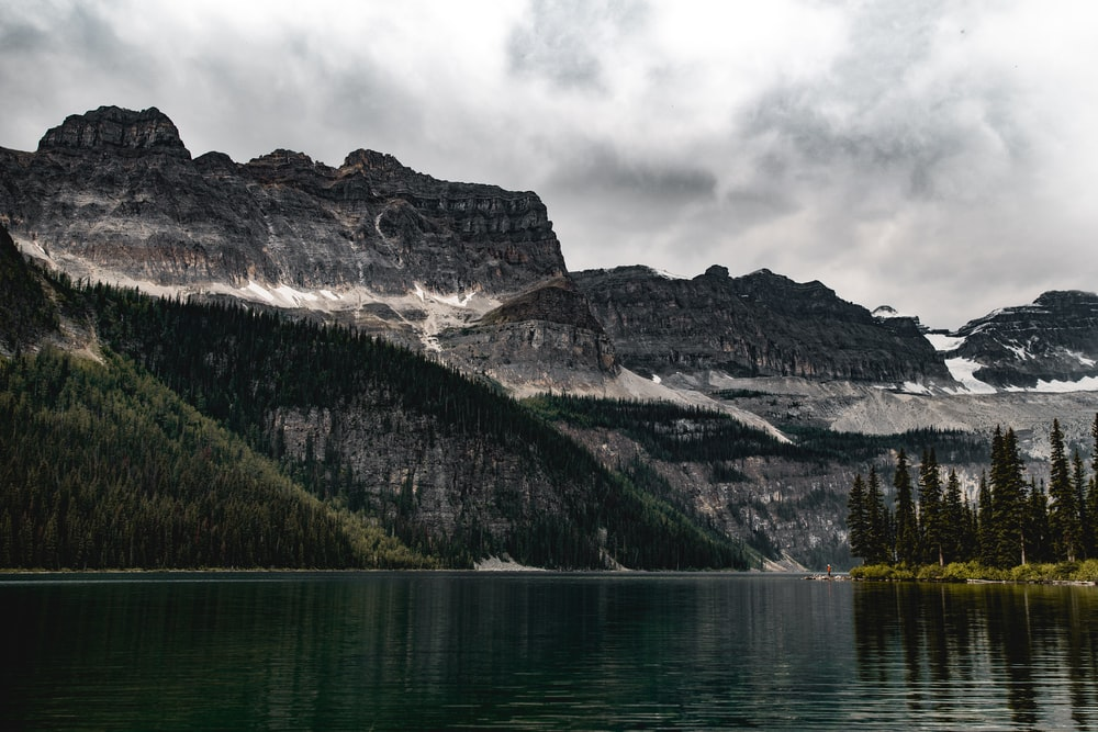 lake near forest and mountain under cloudy sky
