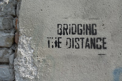 bridging the distance text on gray concrete surface close-up photography