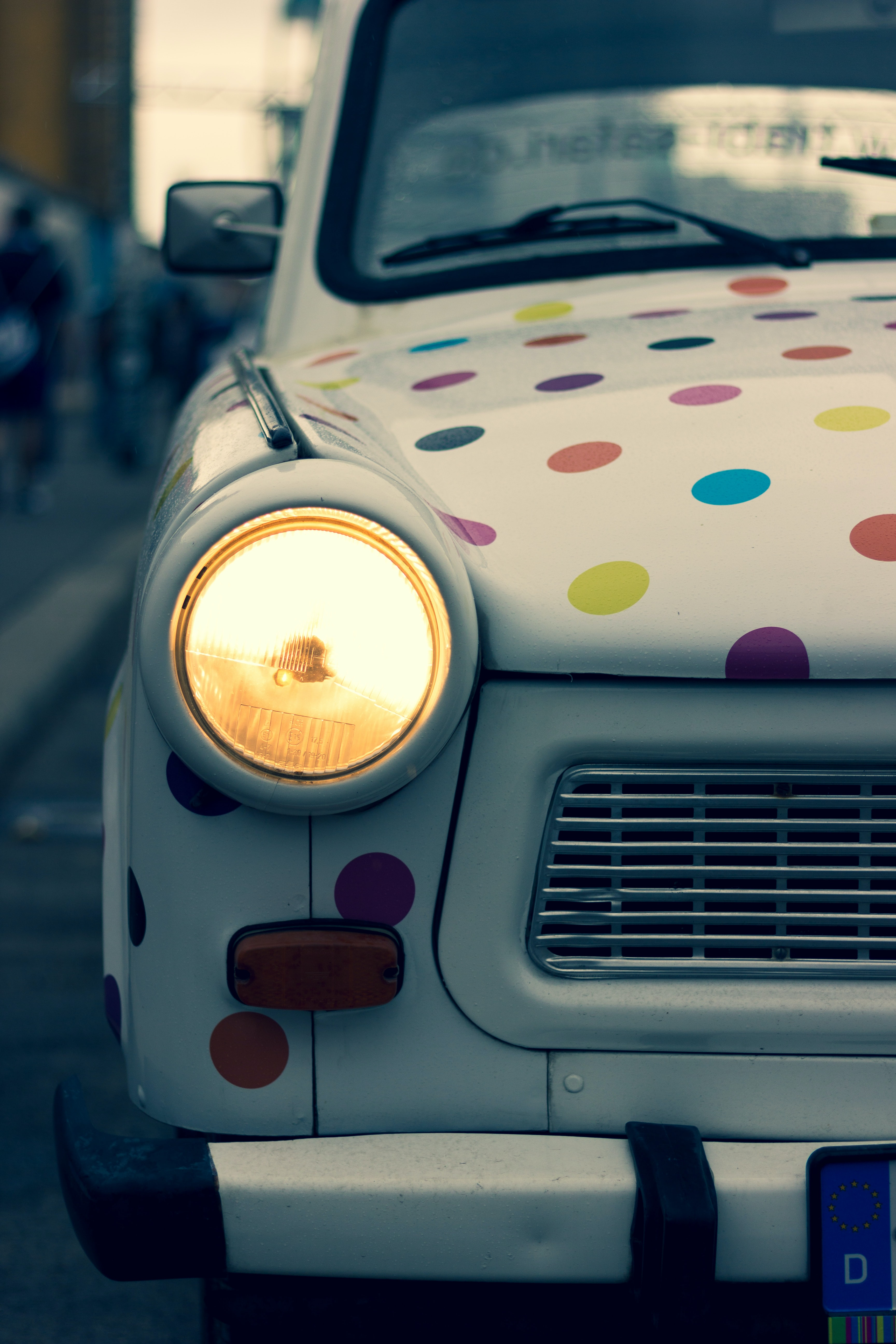 white and multicolored polka-dot vehicle with turned on headlight