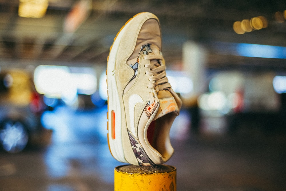 brown Nike running shoe on yellow pole