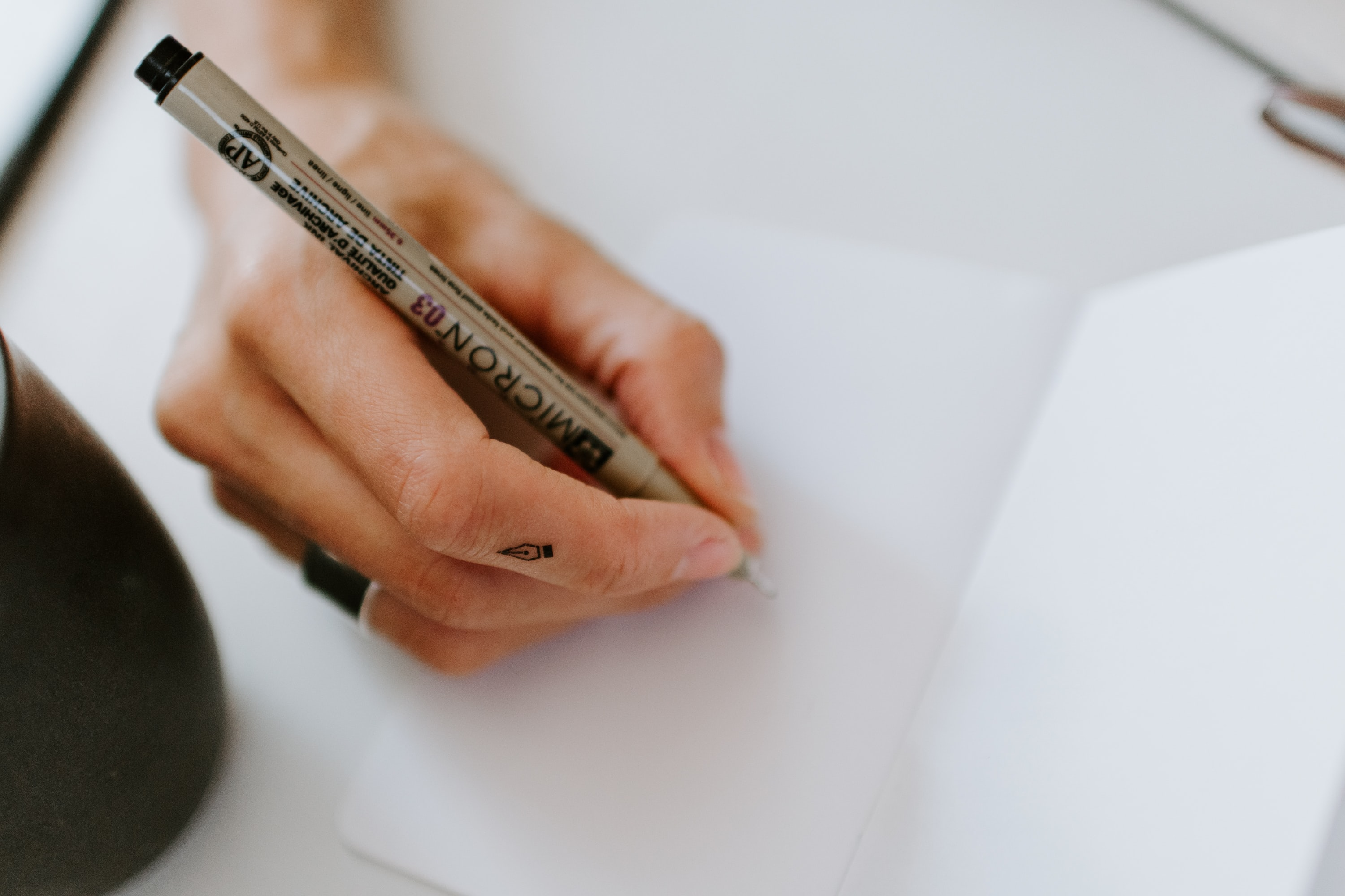 person using pen on white paper