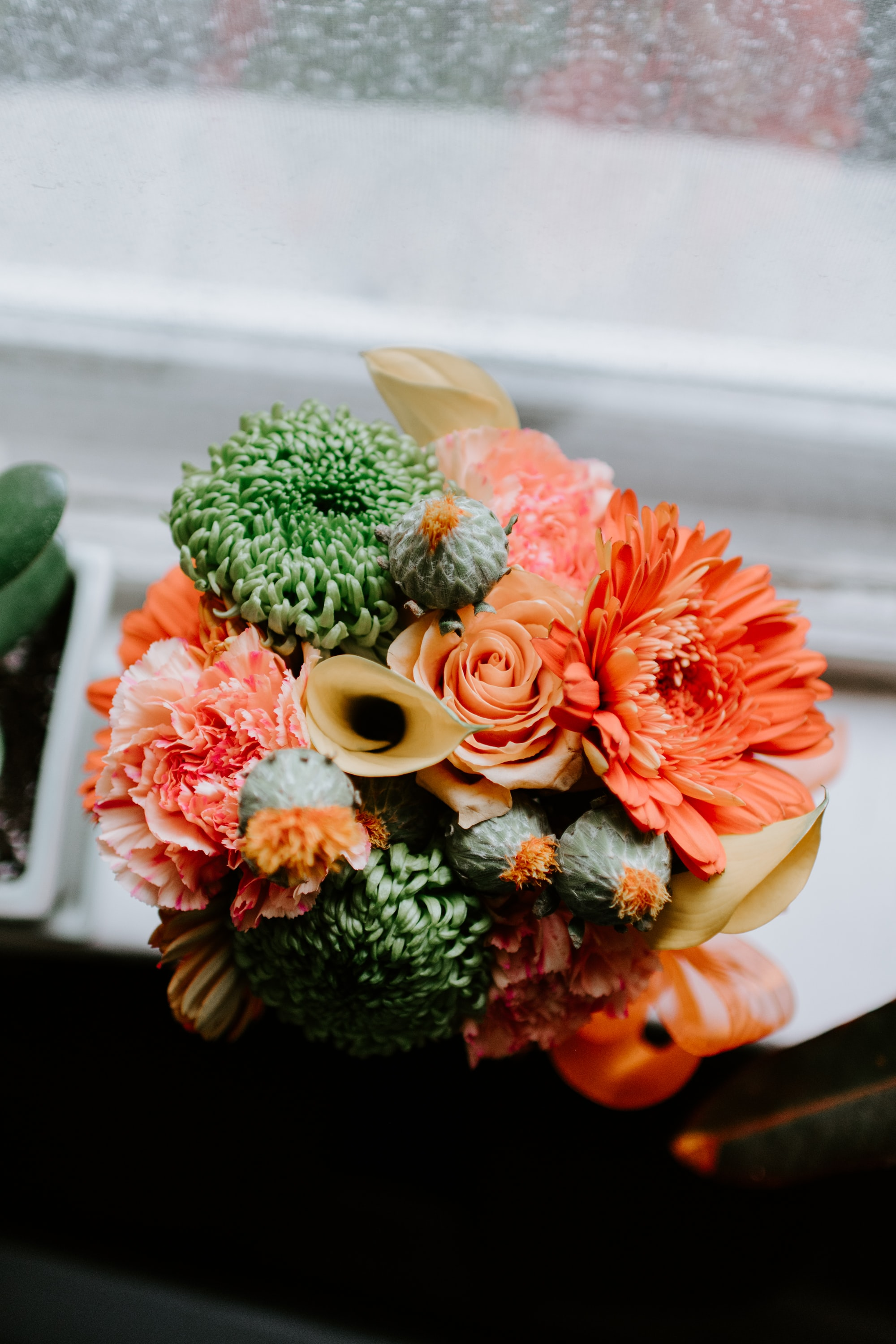 yellow, green, and beige artificial flower bouquet on white surface