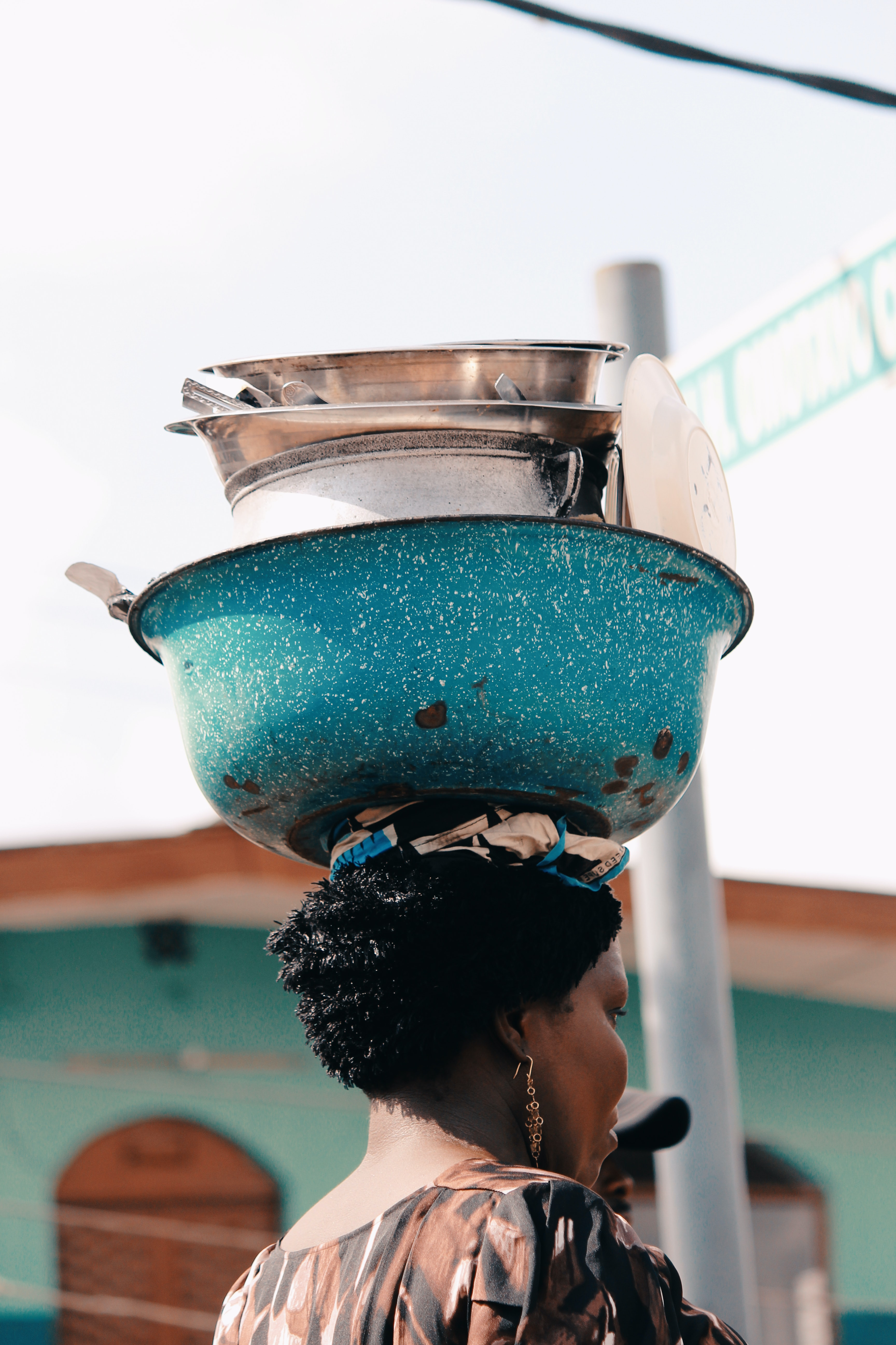 teal steel bowl on woman's head
