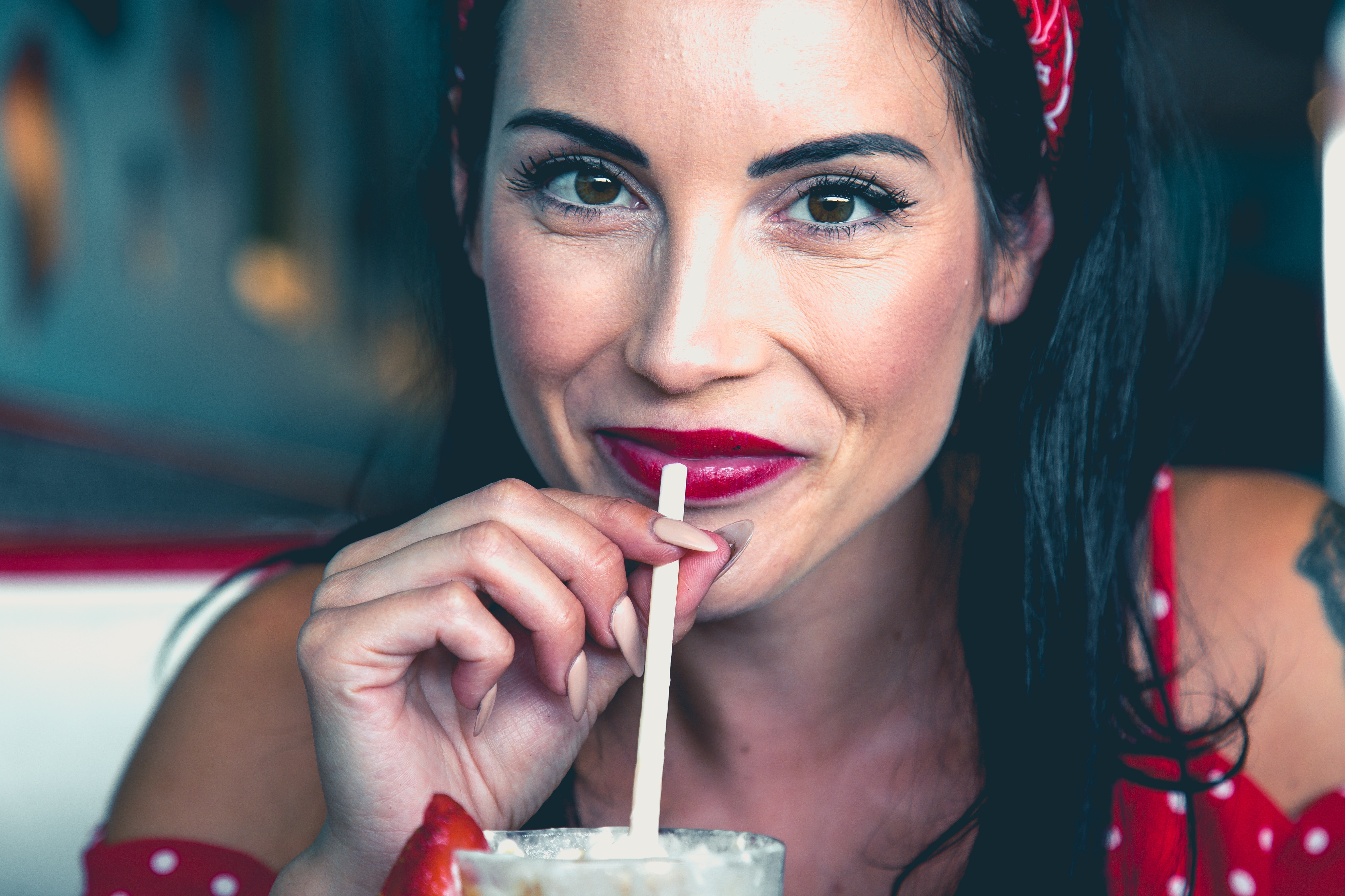 woman wearing red and white polka-dot top holding straw close-up photo