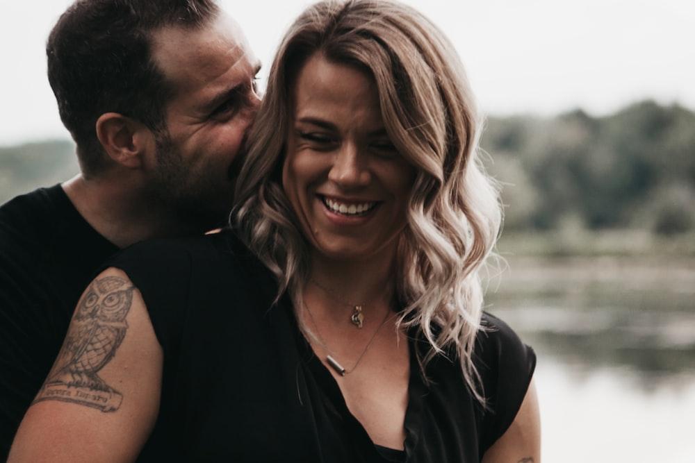 man hugging woman beside body of water