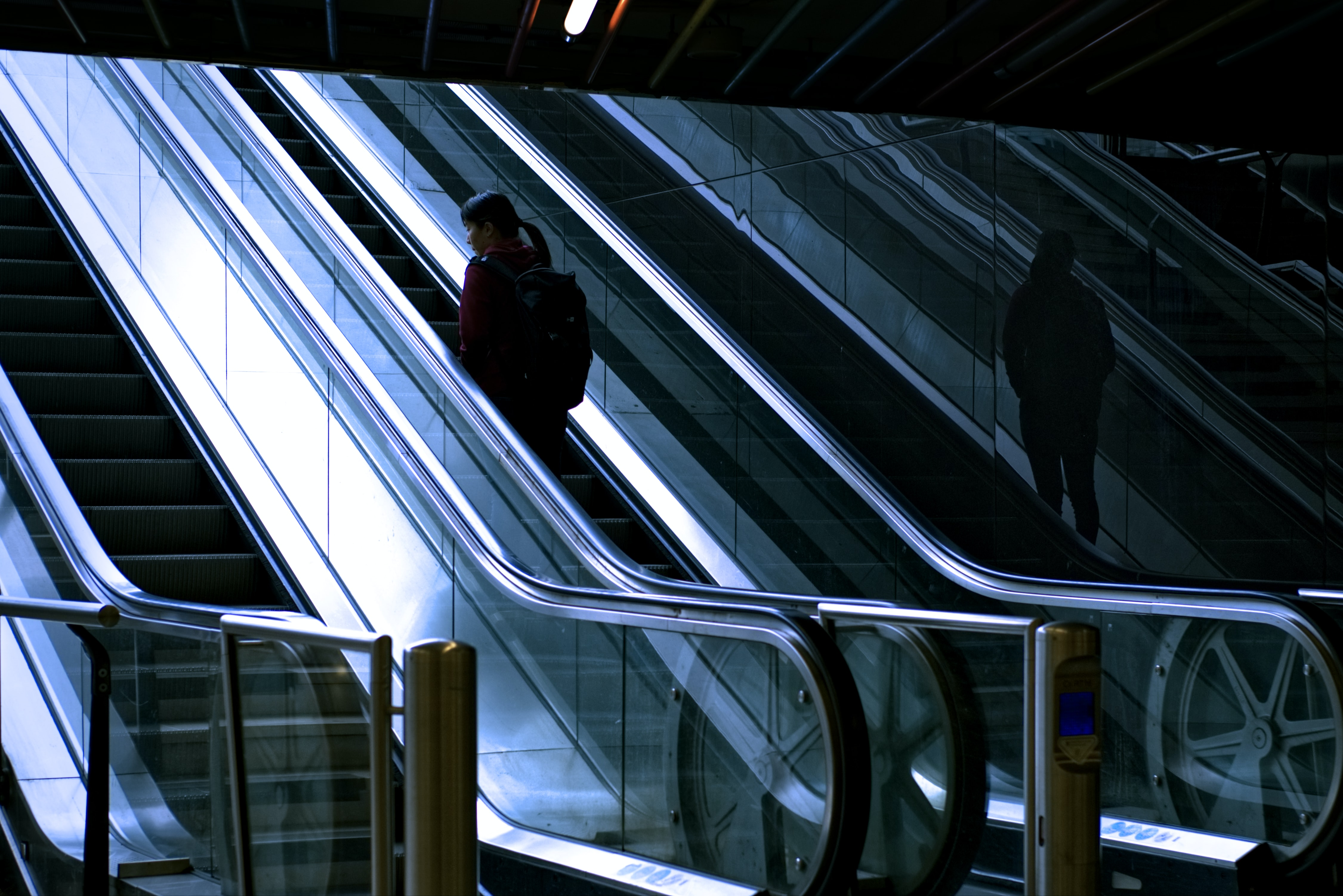 woman standing at escalator