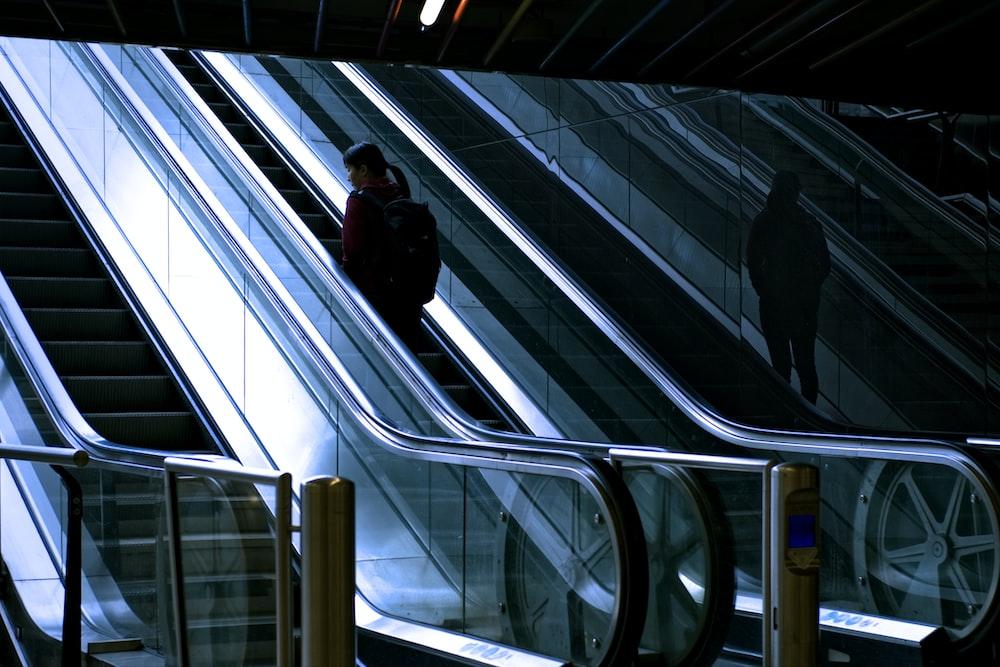 woman standing at escalator