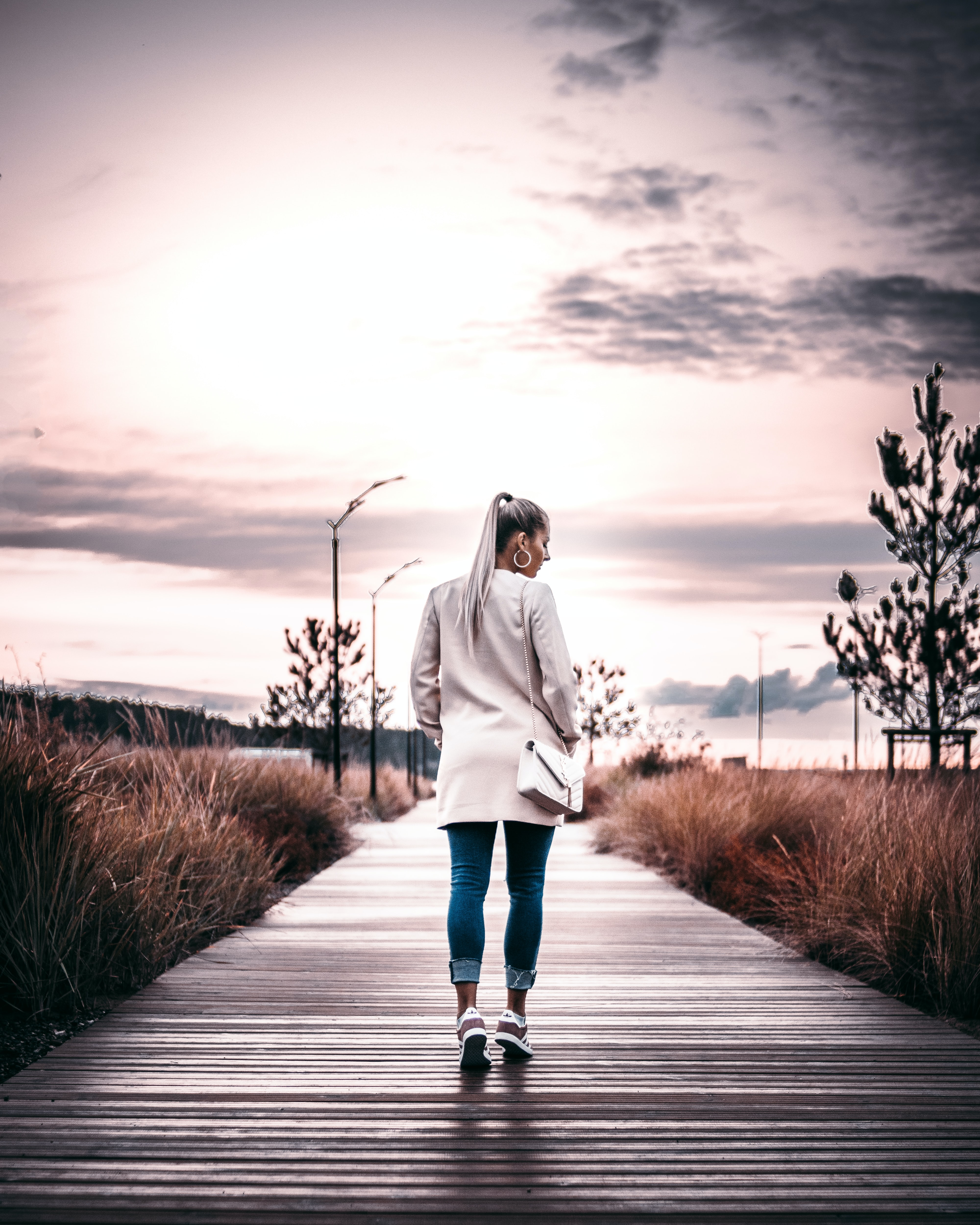 woman wearing white jacket carrying shoulder bag walks on grey concrete road under cloudy sky