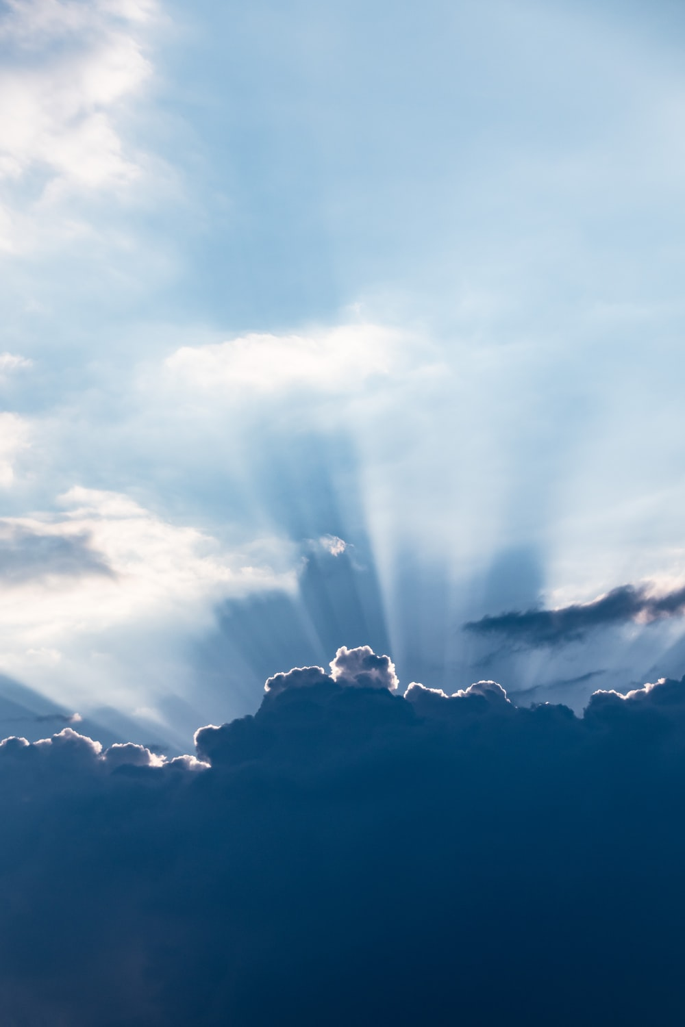 sun rays above silhouette of clouds