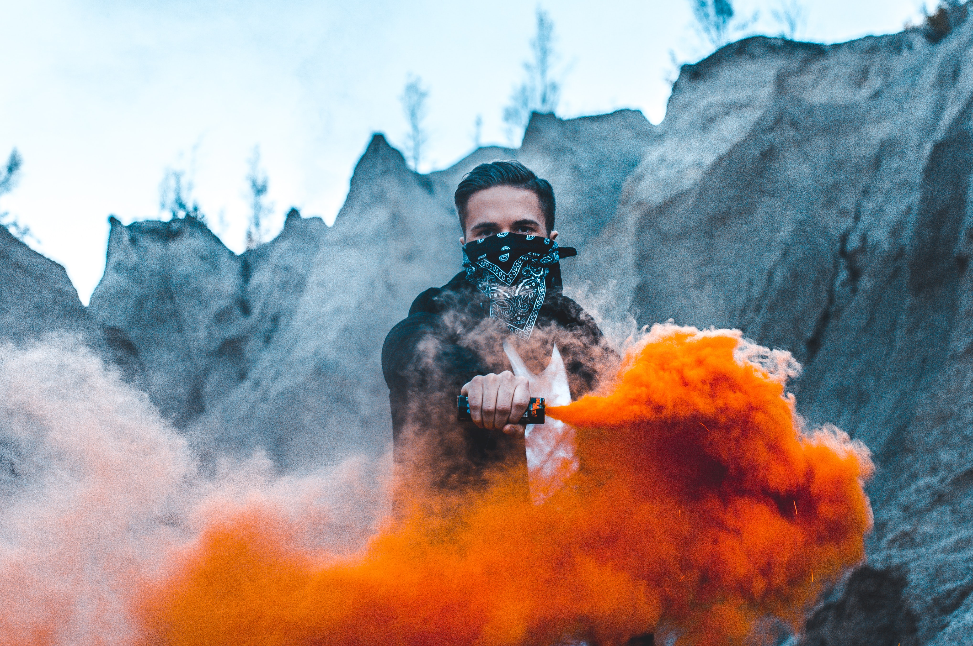 man holding a black vaporizer with orange smoke