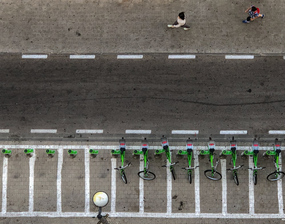 aerial photo of bicycles park on concrete pavement