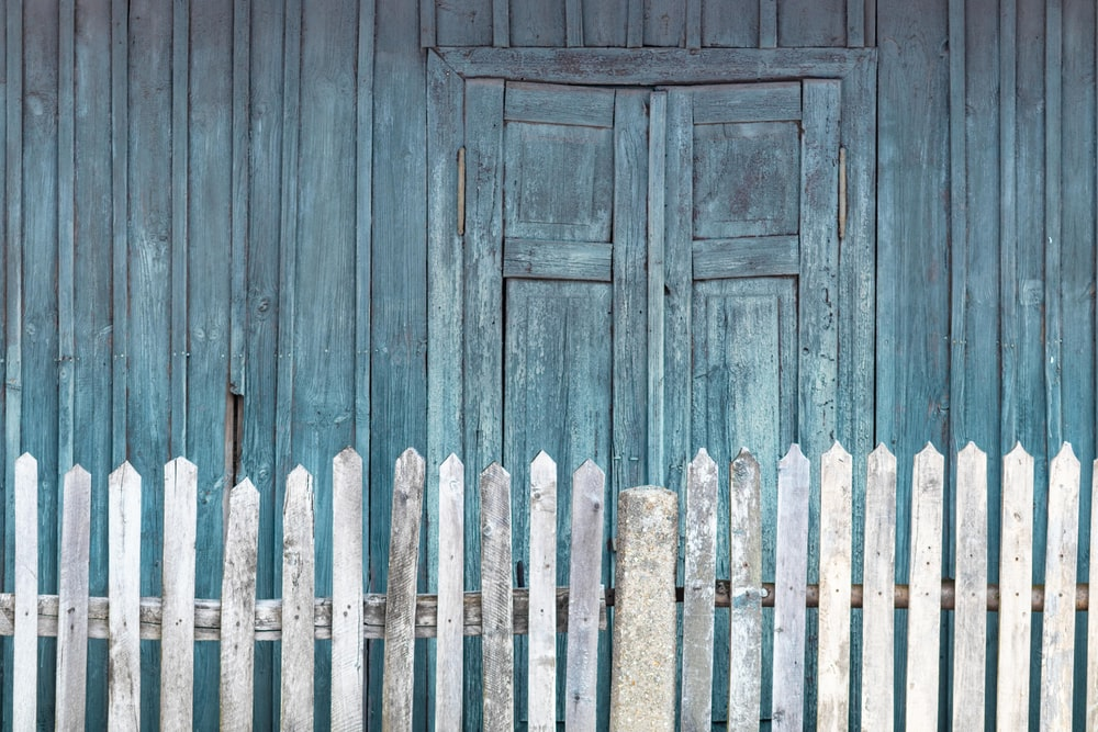 white and beige wooden fence beside wooden shed during daytime