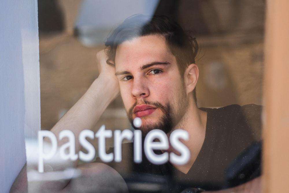 man leaning near clear glass window