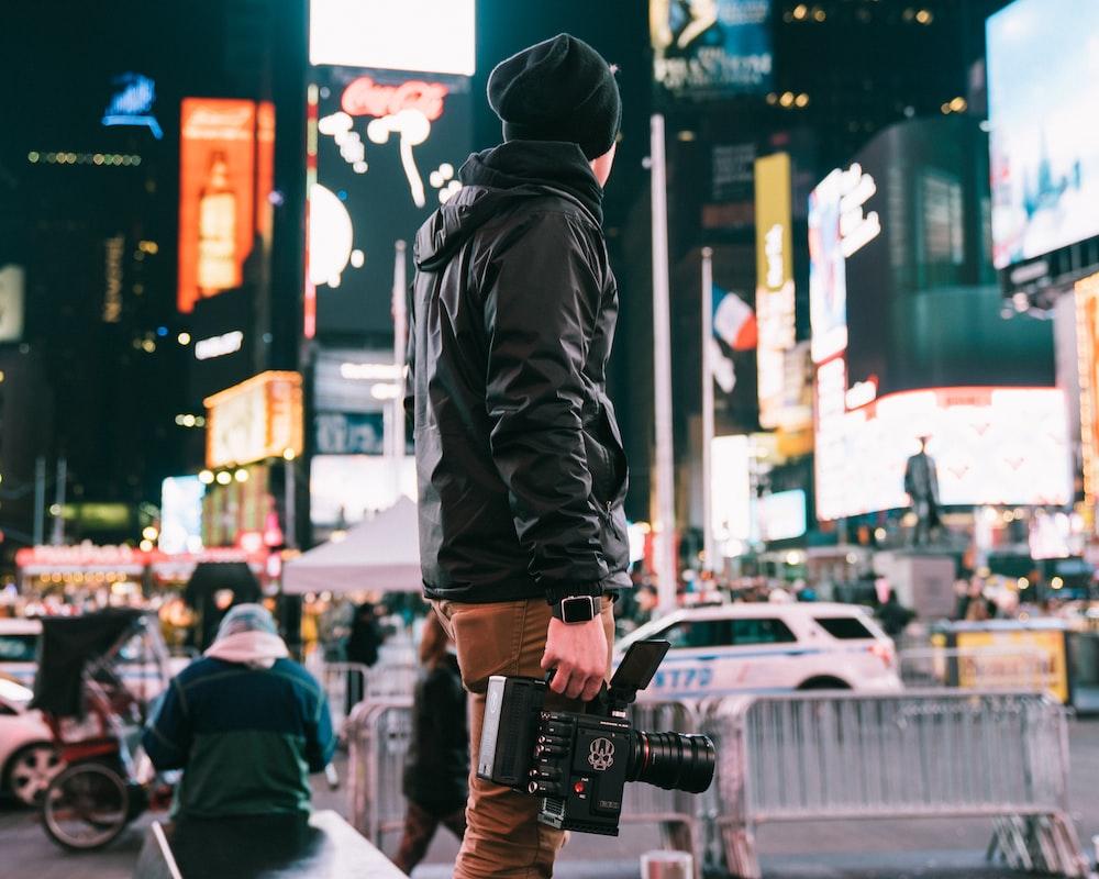 man holding camera looking at signage