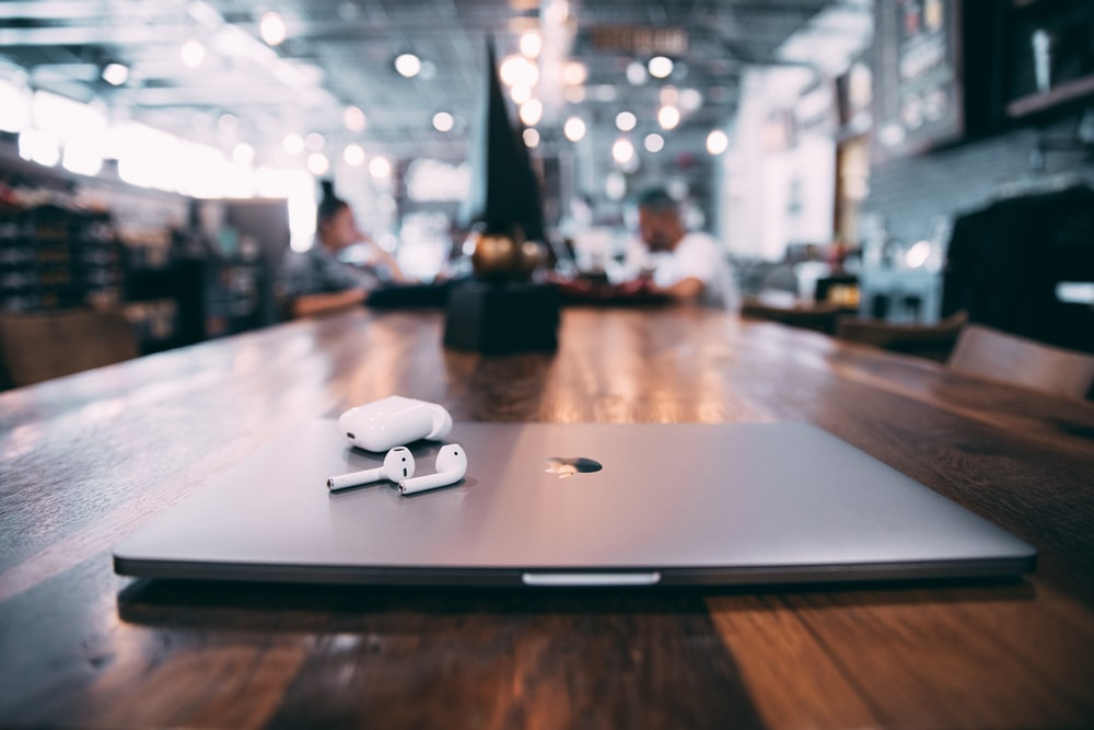 selective focus photography of white AirPods with charging case on silver MacBook on table