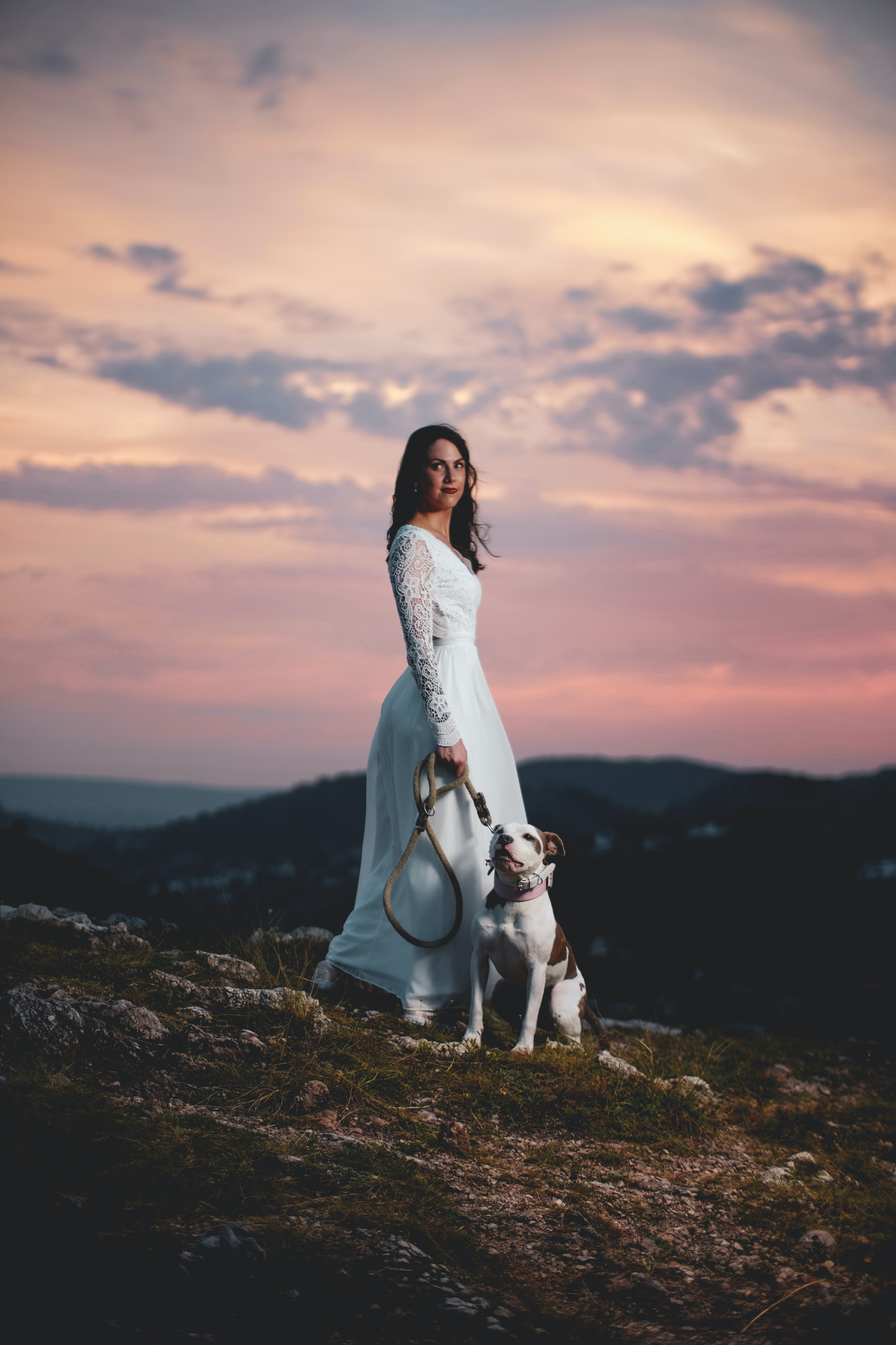 woman wearing white lace gown with dog sitting on the ground