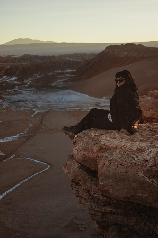 woman sitting on edge of mountain