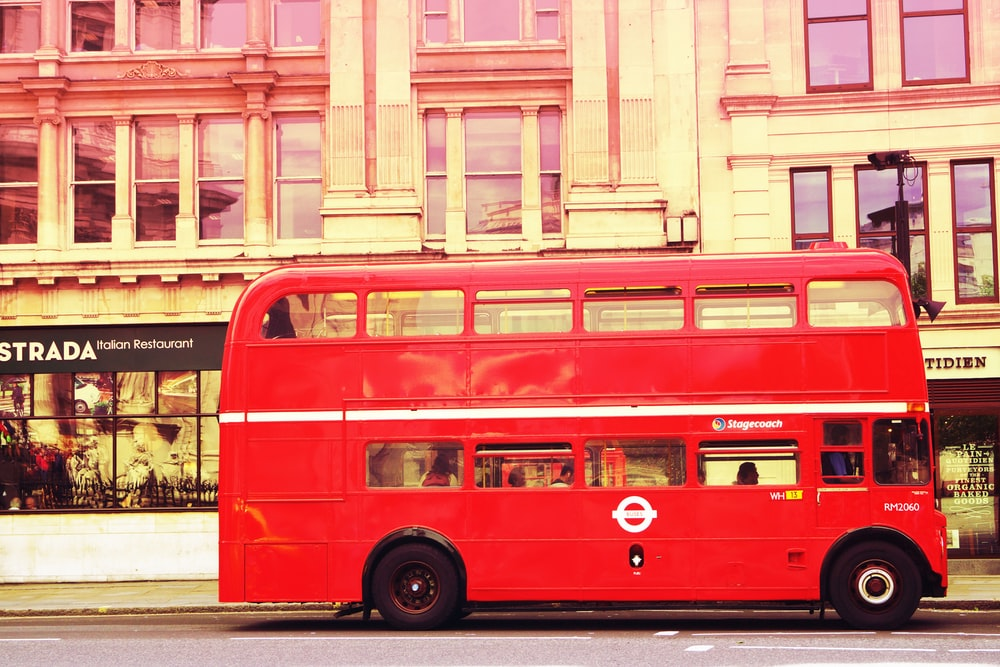 red double deck bus in front of building
