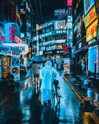 person wearing white raincoat on street while holding bicycle between high-rise building