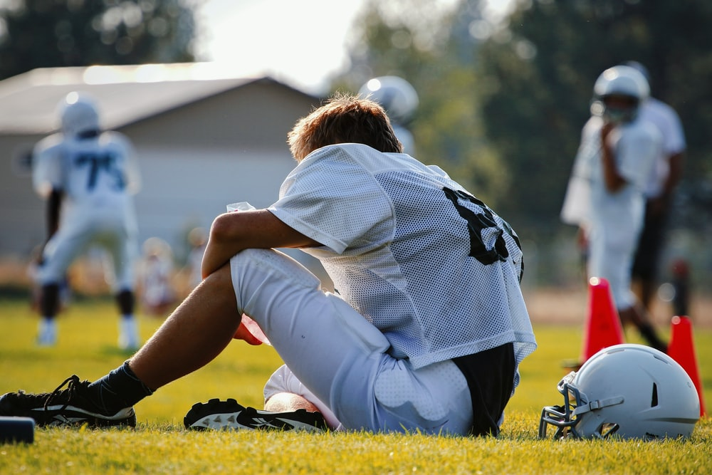 selective focus photography of man sitting on field wearing football gear