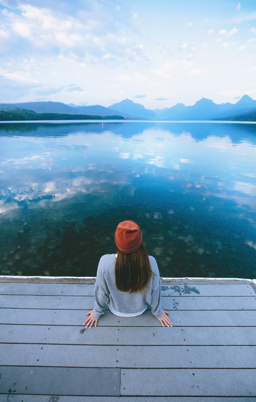 woman sitting in front of calm body of water