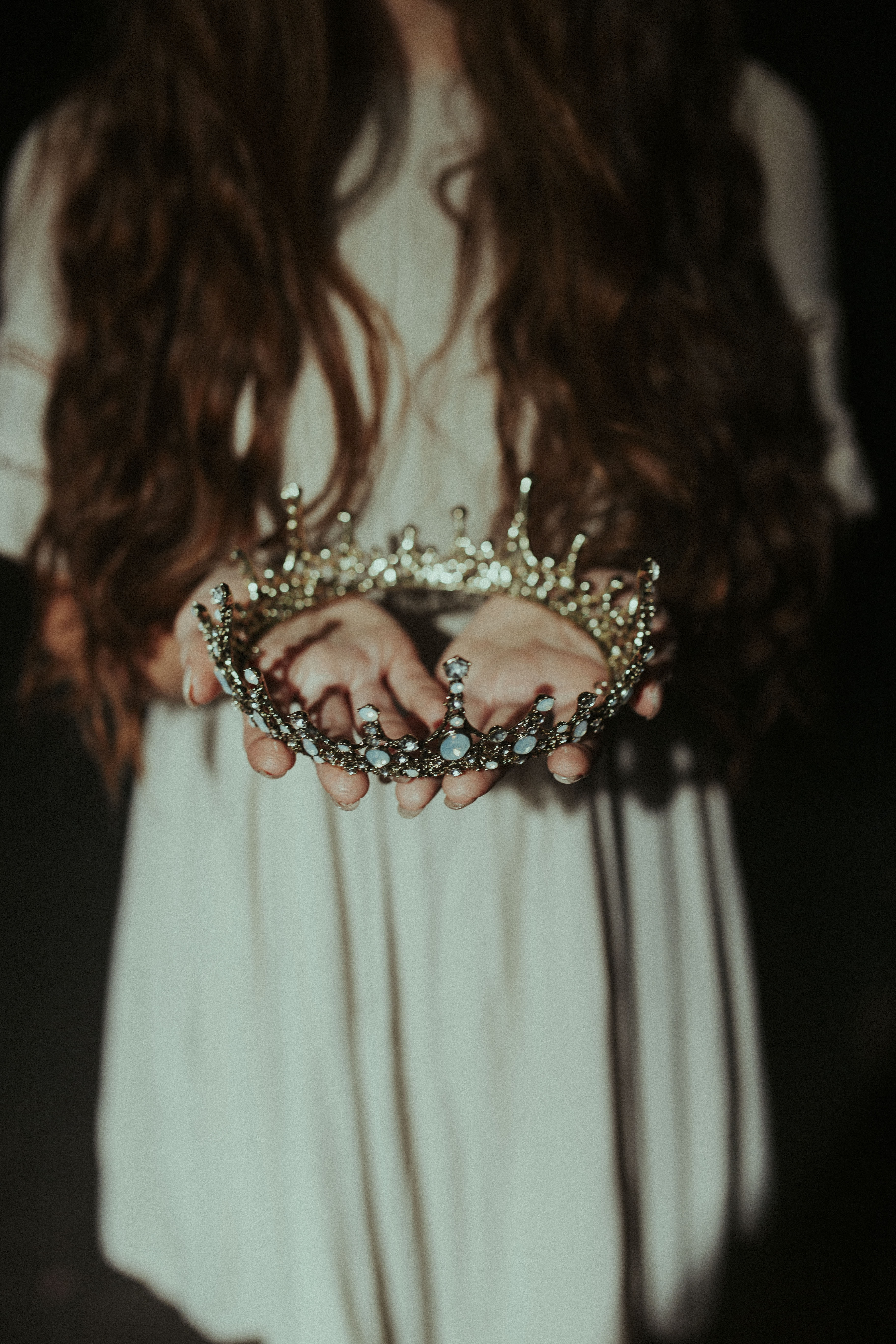 woman holding silver-colored crown
