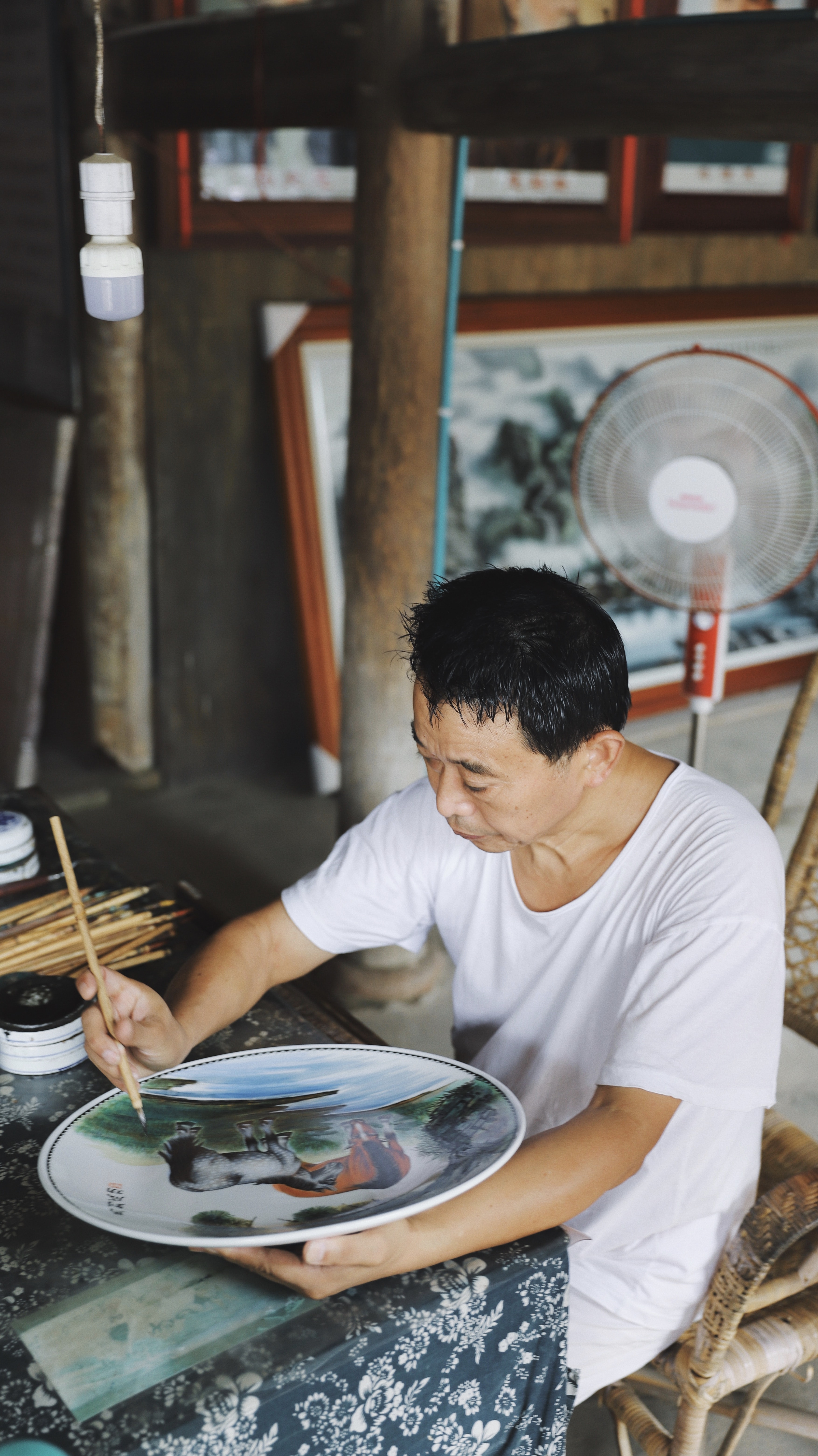 man sitting on chair while painting on plate