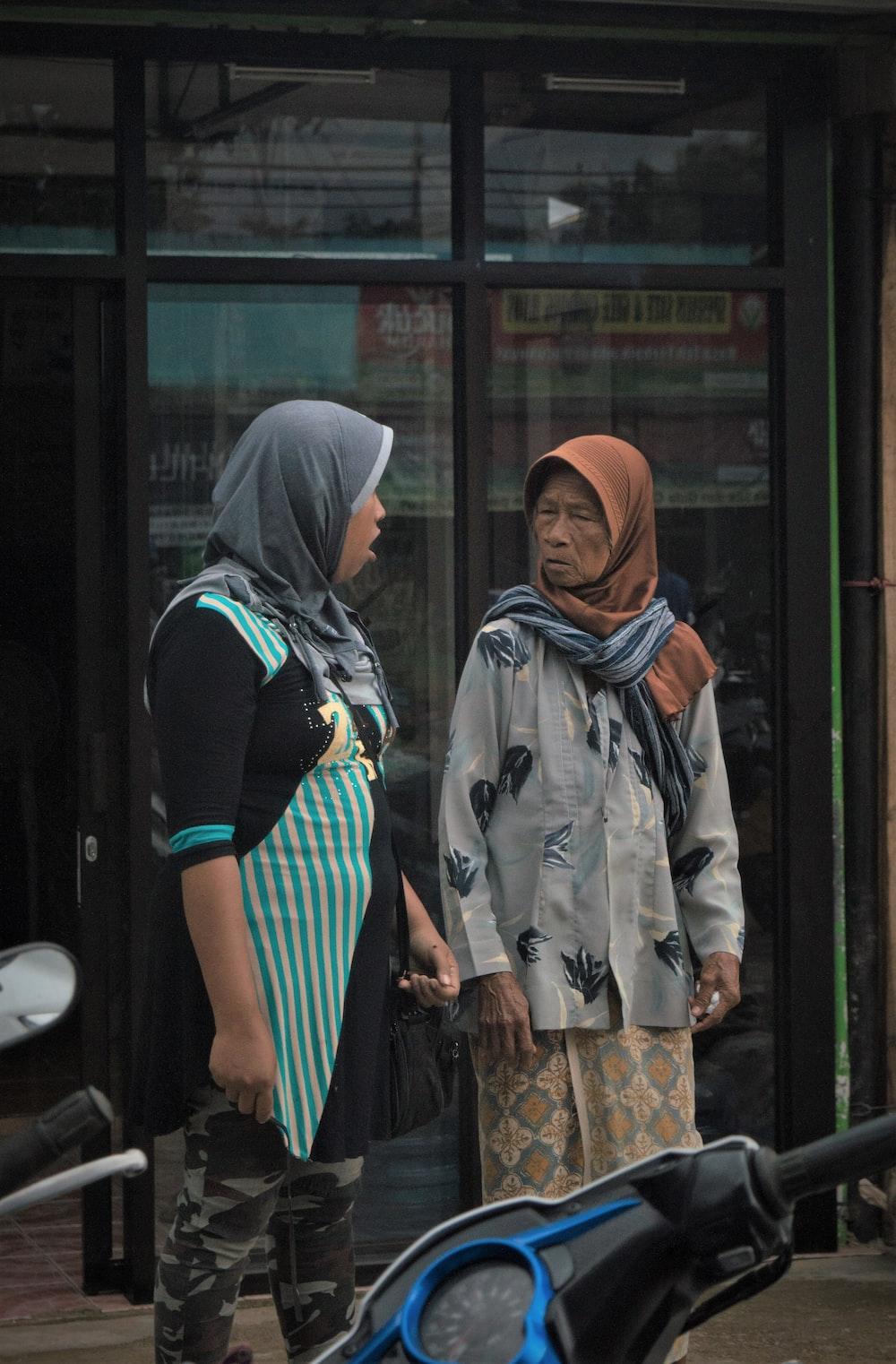two person having conversation near glass door