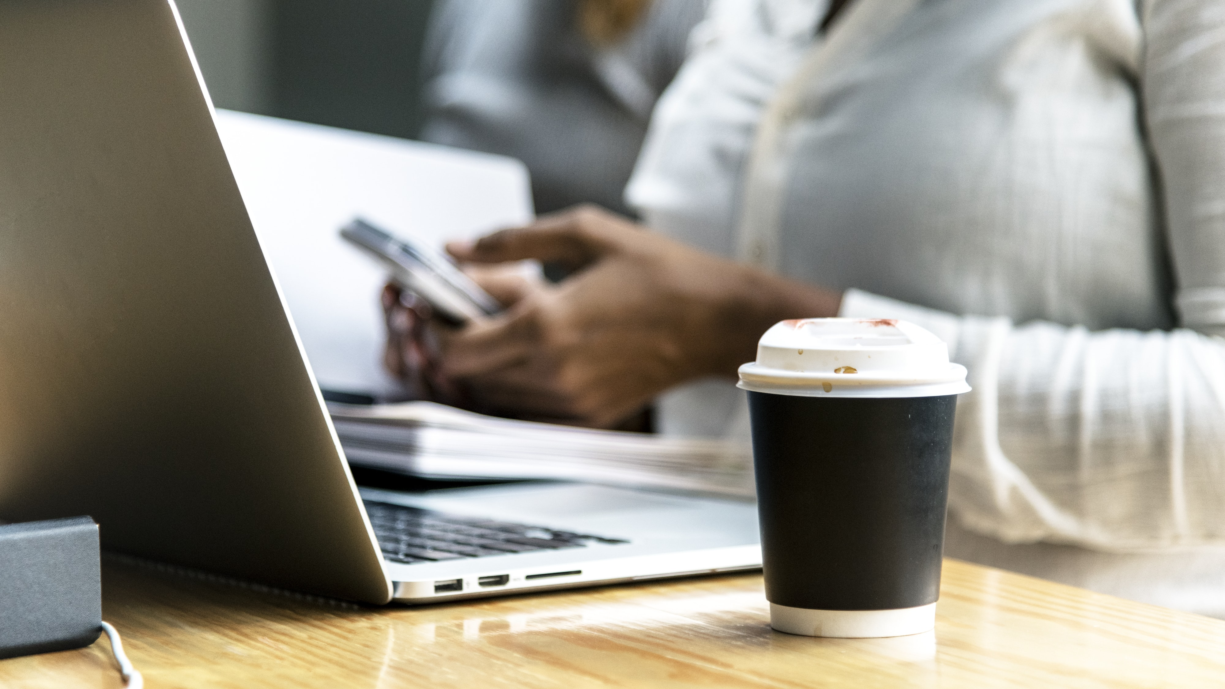 black and white coffee cup beside silver laptop