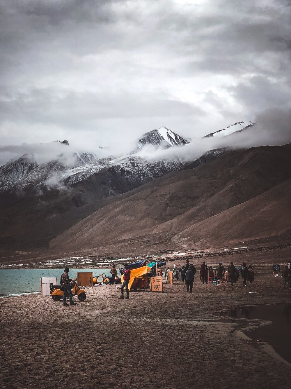 group of person beside mountain under cloudy sky