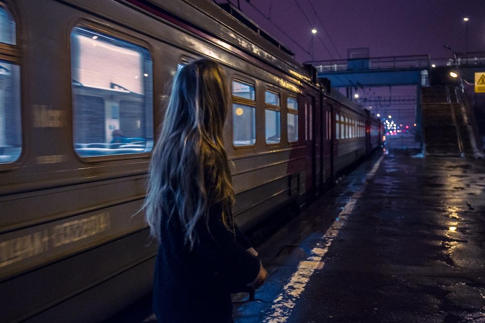 woman standing beside gray train