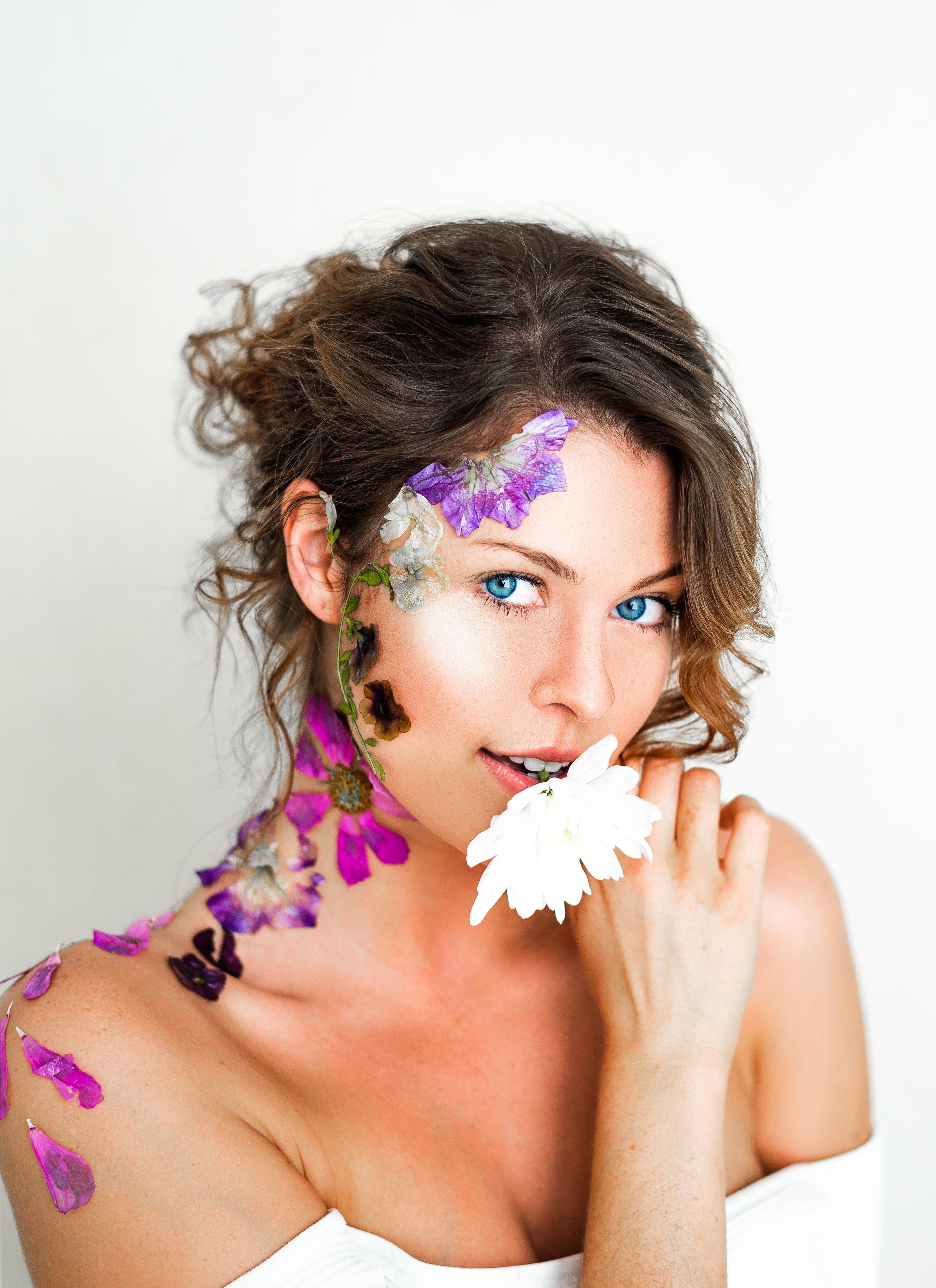 woman biting white flower