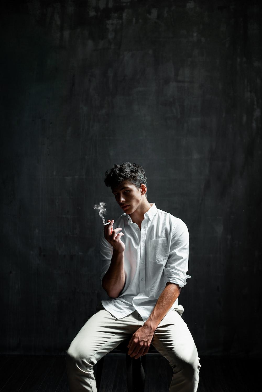 man sitting on chair smoking cigar