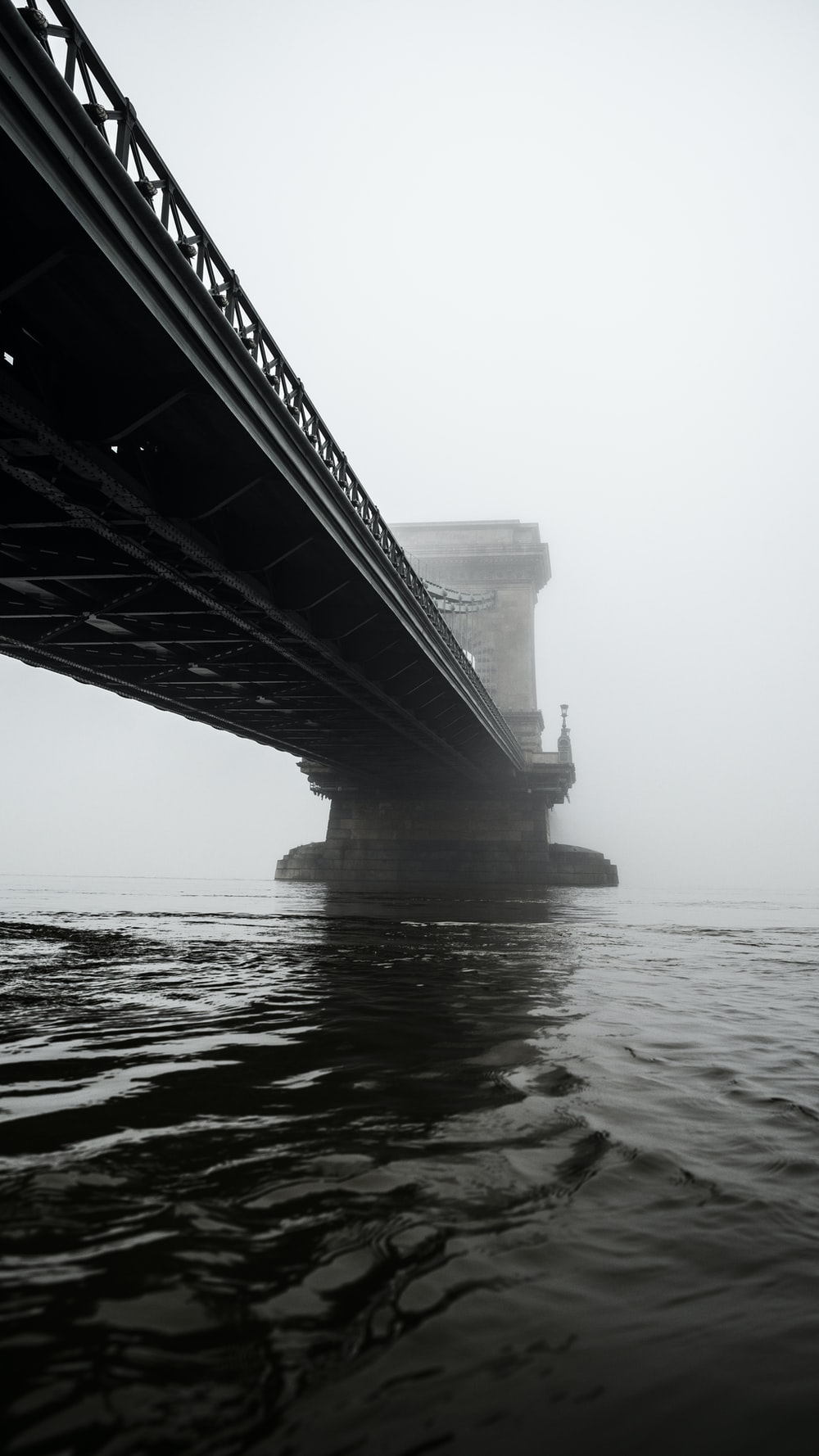 grayscale photography of suspension bridge across calm water