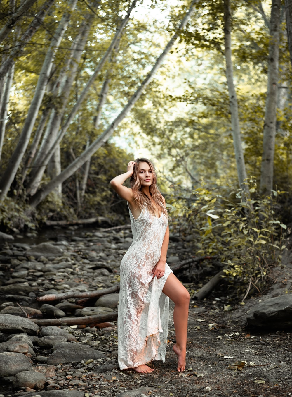 woman in white floral slit dress standing near trees