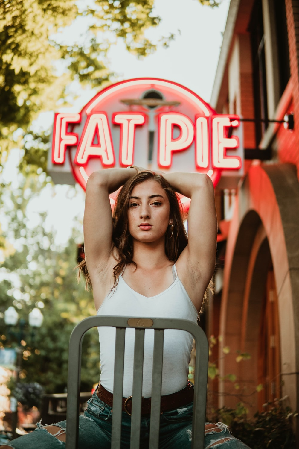 woman sitting on chair raising two arms near fat pie store