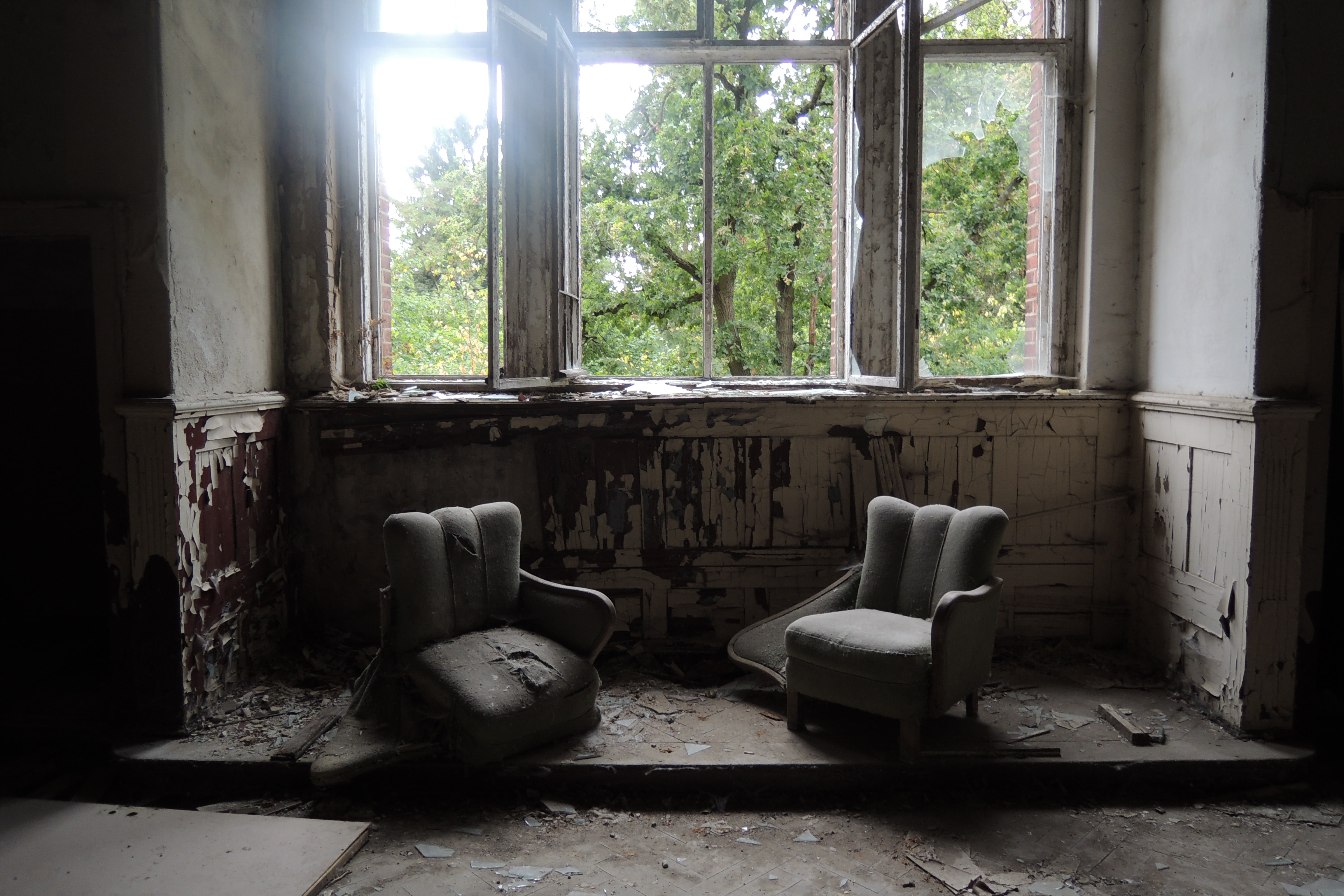 two gray sofa chairs inside wrecked room