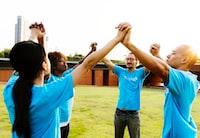 four person raising their hands