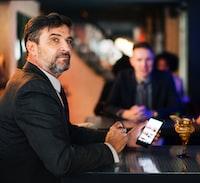 man holding black smartphone while sitting