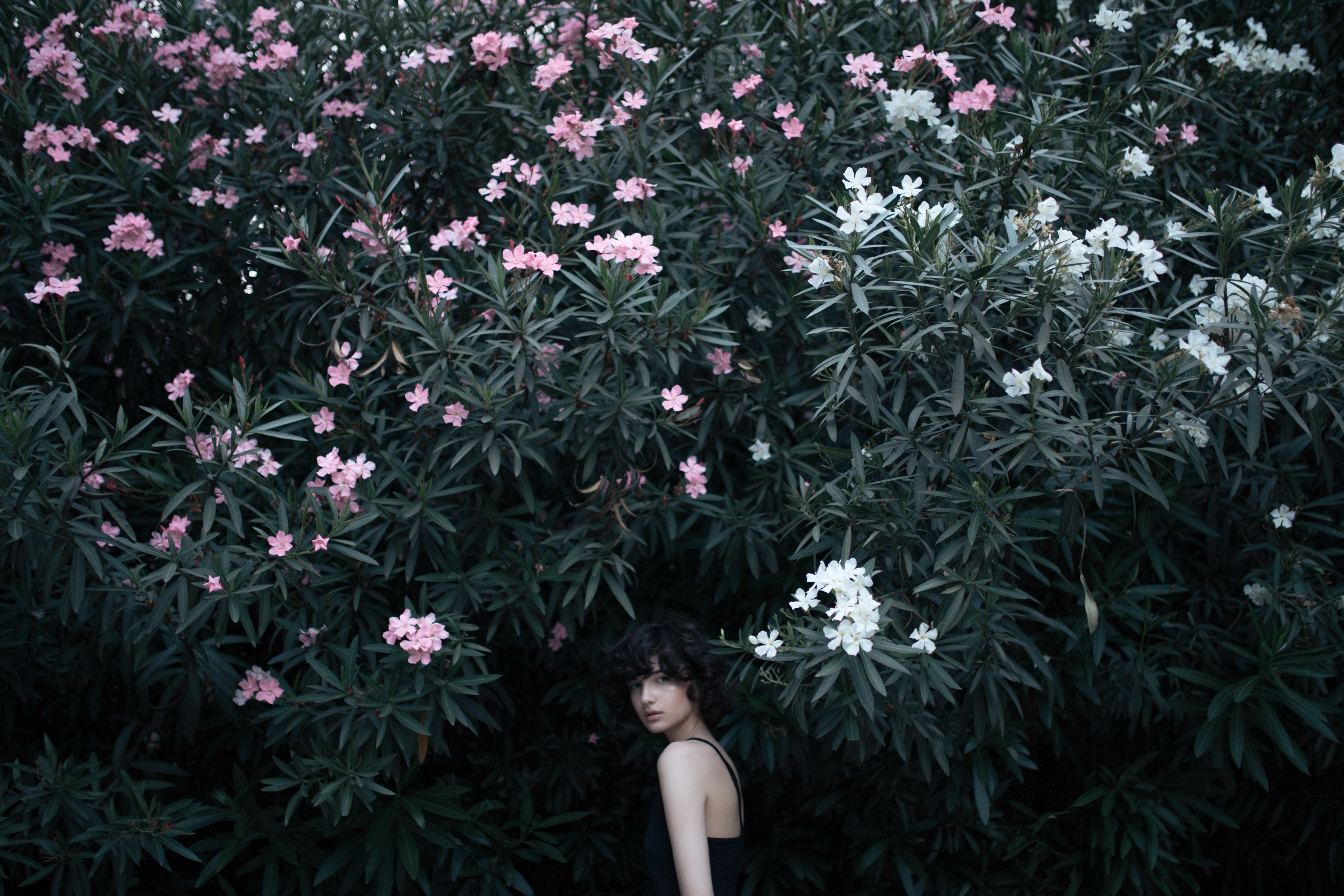 woman looking backwards while walking towards trees