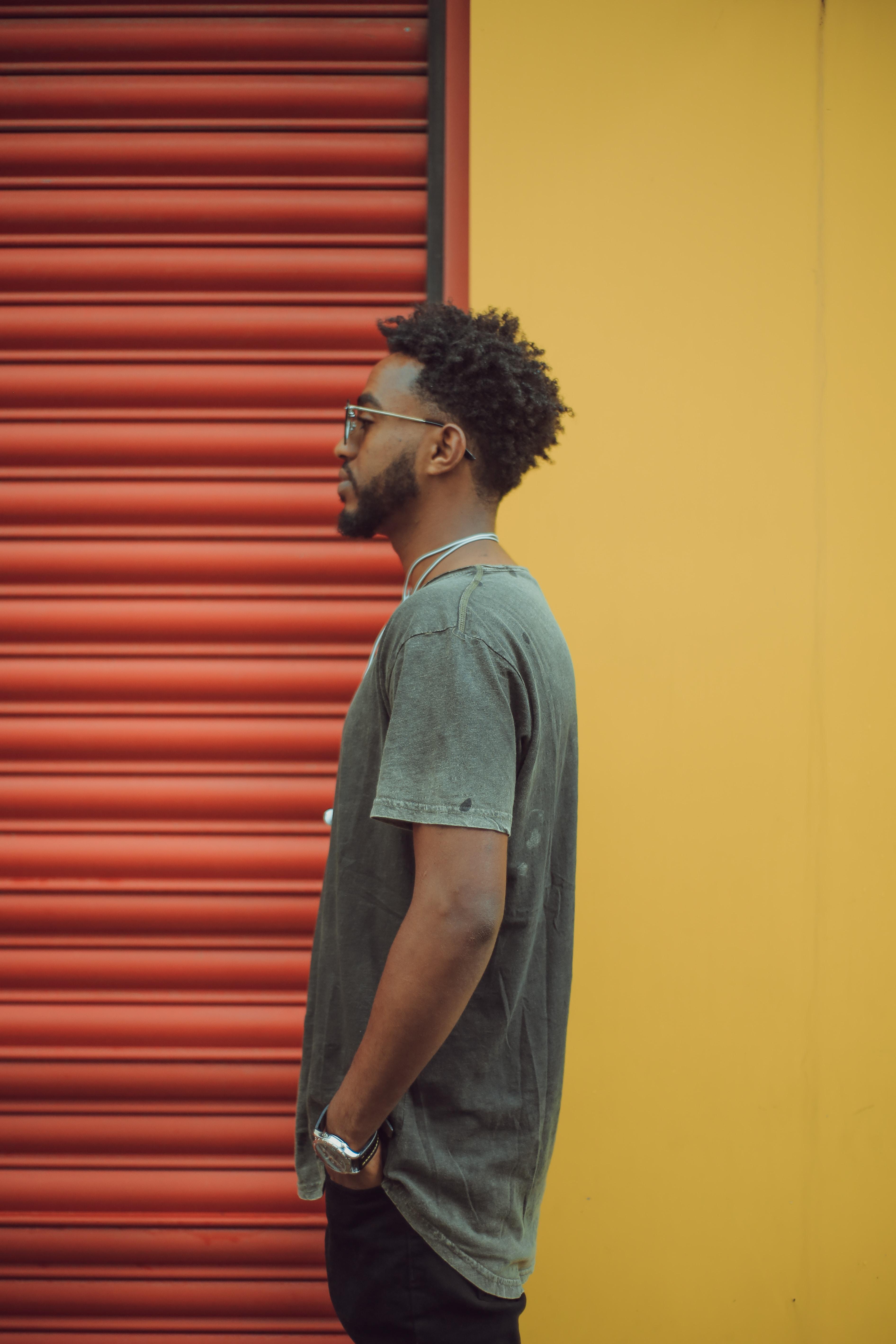 man in gray t-shirt standing near red roll up door