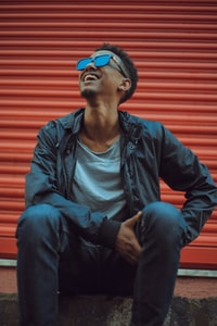 smiling man sitting on concrete floor