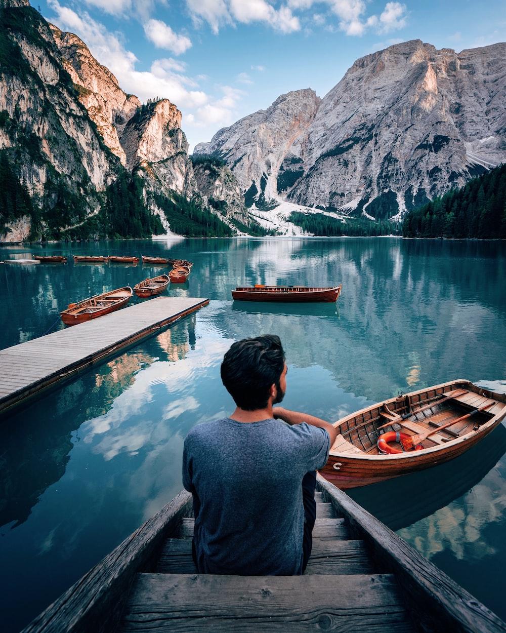 man sitting on brown wooden stairs staring out lake near mountain during daytime