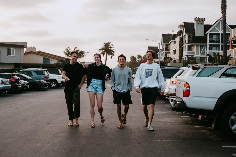 four person walking near vehicle